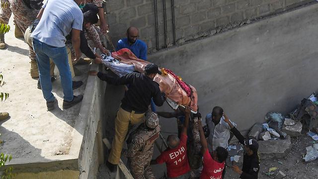 עובדי הצלה מעבירים גופה מהתרסקות המטוס בפקיסטן (צילום: AFP)