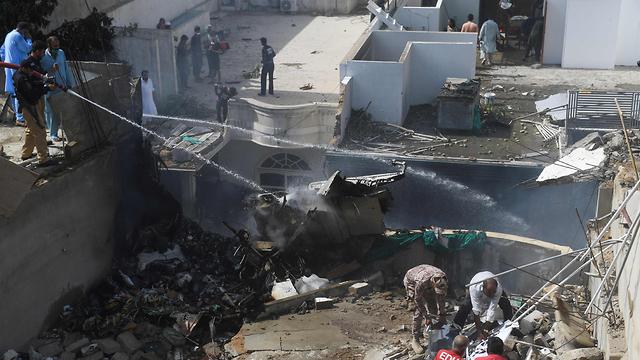 שוטרים ריססו מים על מטוס הנוסעים שהתרסק בפקיסטן (צילום: AFP)