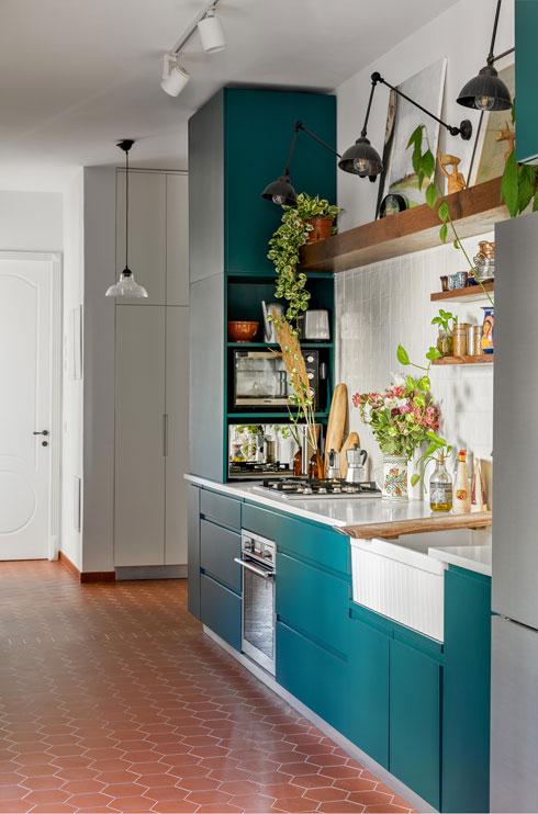 מלבד הרצפה, המטבח, בגוון טורקיז כהה, הוא נקודת הצבע היחידה. כדי לקשר בינו לבין הריהוט נוספו לו מדפי עץ עבים (צילום: עידו אדן)