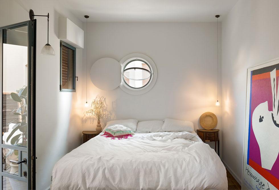 חדר השינה. מצדי המיטה שידות עץ משוק הפשפשים ומעליהן תלויות שתי מנורות ליה זעירות. חלון הספינה הוא חלק מהאדריכלות המקורית של הבניין וחוזר בחדרים השונים (צילום: עידו אדן)
