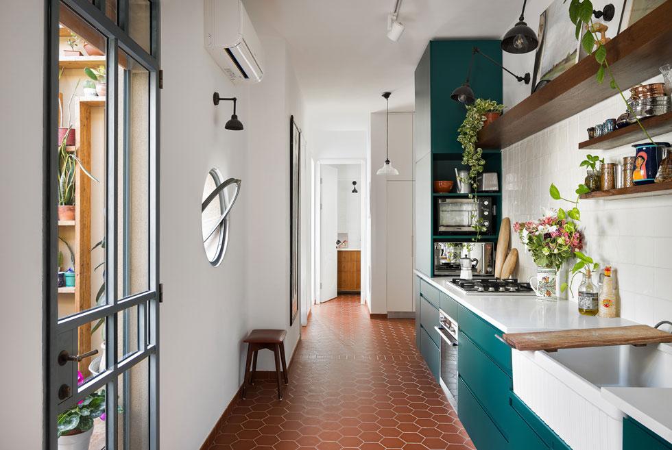 מרצפות הטרקוטה נמשכות מהסלון אל המטבח, המסדרון ולתוך חדר הרחצה שבקצה הדירה (צילום: עידו אדן)