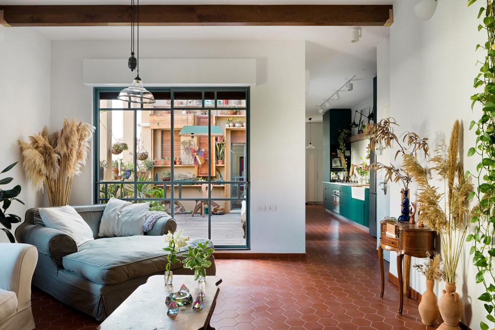 ארונות מטבח בירוק עז הם נקודת הצבע הבולטת בדירה. הפטיו עוצב בסגנון חופשי ומחוספס יותר (צילום: עידו אדן)