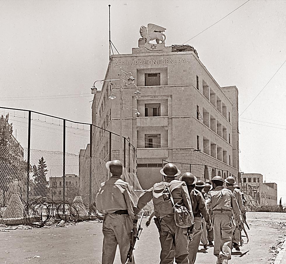 בניין ג'נרלי על רקע כניסת כוחותינו לאזור אחרי עזיבת הבריטים 14.5.48 (צילום: רודלף יונס, באדיבות ארכיון קק