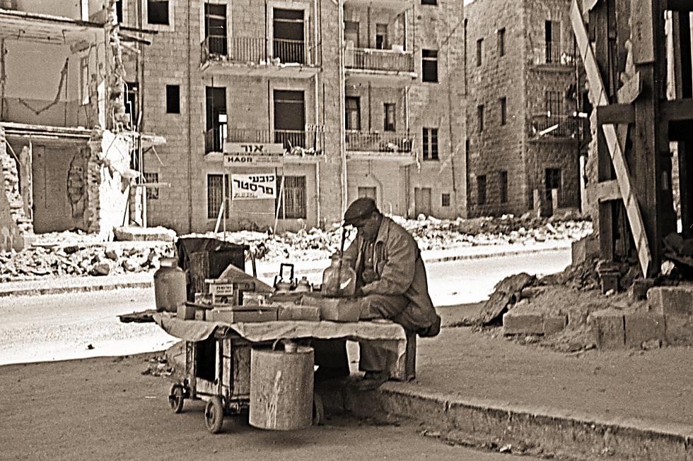 חנווני מסדר את מרכולתו ברחוב בן יהודה זמן קצר לאחר הפיגוע 1948 (צילום: אדגר הירשביין, באדיבות ארכיון קק