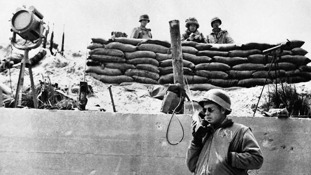 איש רפואה אמריקני מדבר עם המפקדה ומבקש אספקה, בחופי נורמנדי (צילום: AP)