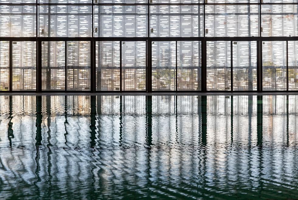 זו הבריכה הציבורית הראשונה בעיר שמציעה לשחיינים נוף אורבני בכל יציאה של הראש מהמים, כי מדובר בקומה 3. החרכים הכמו-אקראיים בסבכה מסתירים ומגלים בכל פעם פריים אחר (צילום: דור נבו)