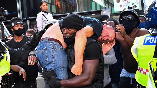בריטניה לונדון מהומות ג'ורג' פלויד מפגין שחור נושא פעיל ימין קיצוני שהוכה ונפצע (צילום: רויטרס)