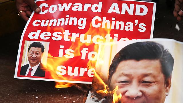 הודו מפגינים הודים שורפים תמונה של נשיא סין שי ג'ינפינג אחרי עימות קטלני ב הימלאיה (צילום: EPA)
