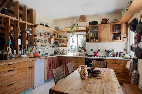 מדפים פתוחים מחברים במבט בין המטבח לכניסה (צילום: שירן כרמל)