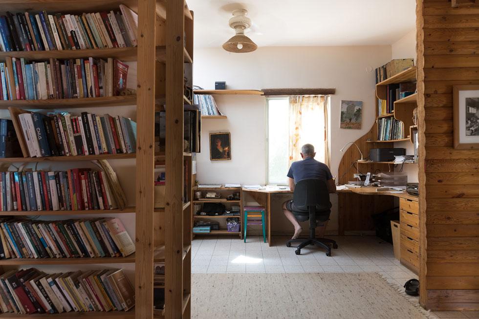 עוזי ליד שולחן הכתיבה שלו. את כל עבודות העץ בבית עשה בעצמו - ארונות וספריות, מדפים ומטבח, מדרגות וחיפויי קיר. ''לא היה לנו כסף, שזה ממש מזל'', אומרת רמה. ''הכל הכי פשוט. אין מה להתלבט'' (צילום: שירן כרמל)