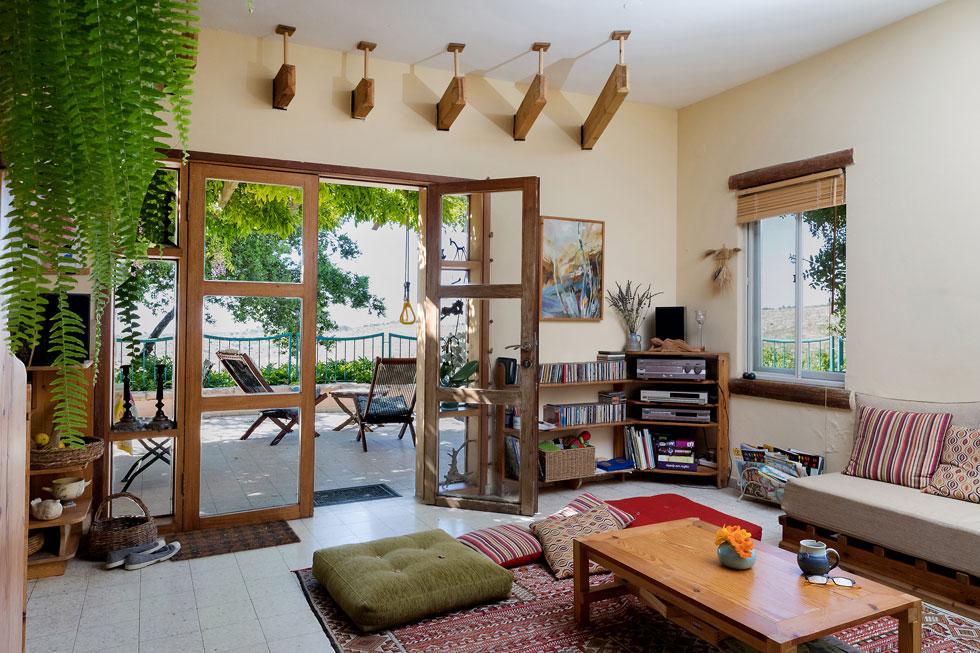 קורות הפרגולה חודרות את מעטפת הבית, ונפרשות בסלון הצנוע כמו מניפה (צילום: שירן כרמל)