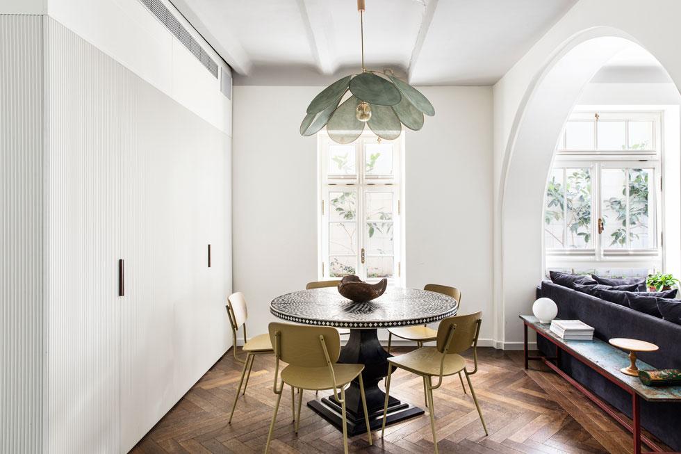 הסגנון האקלקטי של המבנה חודר פנימה: שולחן האוכל מהודו, המנורה מפריז והארונות מודרניים. מימין נראית אחת מהקשתות הפעורות בקירות עבים במיוחד (55 ס''מ) כדי לתמוך את הקומות העליונות (צילום: איתי בנית)