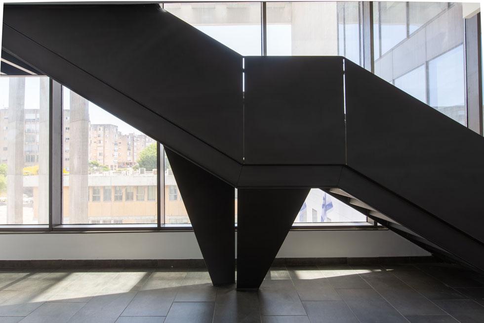 לוחות פלדה דקיקים מרכיבים את גרם המדרגות הקושר בין הקומות, בגוון כהה במיוחד שמזכיר את גלימות השופטים (צילום: דור נבו)
