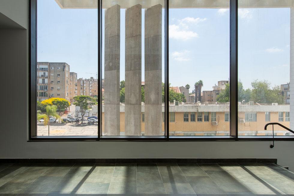 שלושה עמודים דקים מבטון חשוף מתנשאים לכל גובה הבניין ונושאים את המצללה העליונה (צילום: דור נבו)
