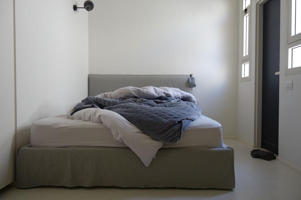 המיטה סתורה, מחשב נייד מונח עליה, למרגלותיה בגדי שינה קצרים שהושלכו לרצפה. קירות חשופים (צילום: מיכאל יעקובסון)