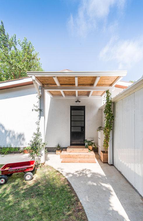 הכניסה. כמו החלונות, הדלת עשויה אלומיניום שחור, וכמו המרפסת, היא מקורה בפרגולת במבוק ומתכת לבנה (צילום: קרין רבנה)