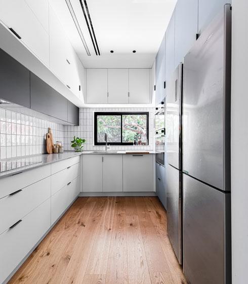 מטבח בצורת ח' במרפסת שנסגרה. התכנון יעיל והחומרים זולים יחסית: ארונות פורמייקה ואריחים פשוטים עם רובה שחורה (צילום: קרין רבנה)
