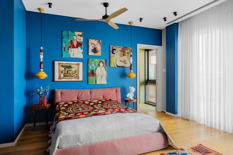 כחול עמוק בחדר השינה של בני הזוג. על הקיר ציורים של לאה בוגנים; שידות הצד וכיסוי המיטה, שעליו רקמה בוכרית, נקנו בשוק הפשפשים (צילום: שירן כרמל)
