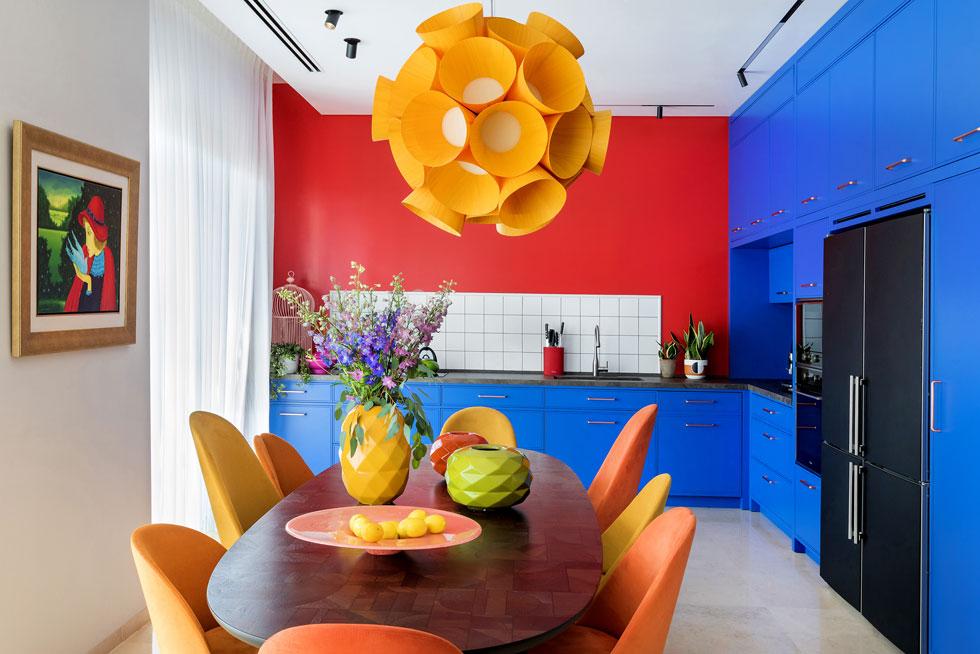 """דווקא עם הצבעים העזים היה קל לשכנע את בני הזוג. """"כשבחרנו כחול לארונות המטבח, הם אלה שהלכו על הכחול הנועז ביותר"""", אומר המעצב. ''הילדים היו בשוק"""", מספרים בני הזוג. ''מתברר שהם יותר סולידיים מאיתנו''. על הקיר ציור מקורי של מאיר פיצ'חדזה (צילום: שירן כרמל)"""