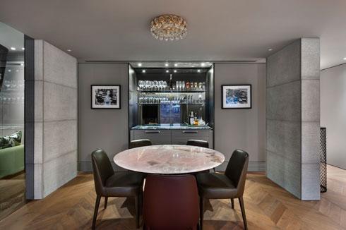 בר משקאות כרקע כהה לפינת האוכל, ותצלומים נוסטלגיים בשחור-לבן תלויים בצורה סימטרית משני צדיו (צילום: עודד סמדר)