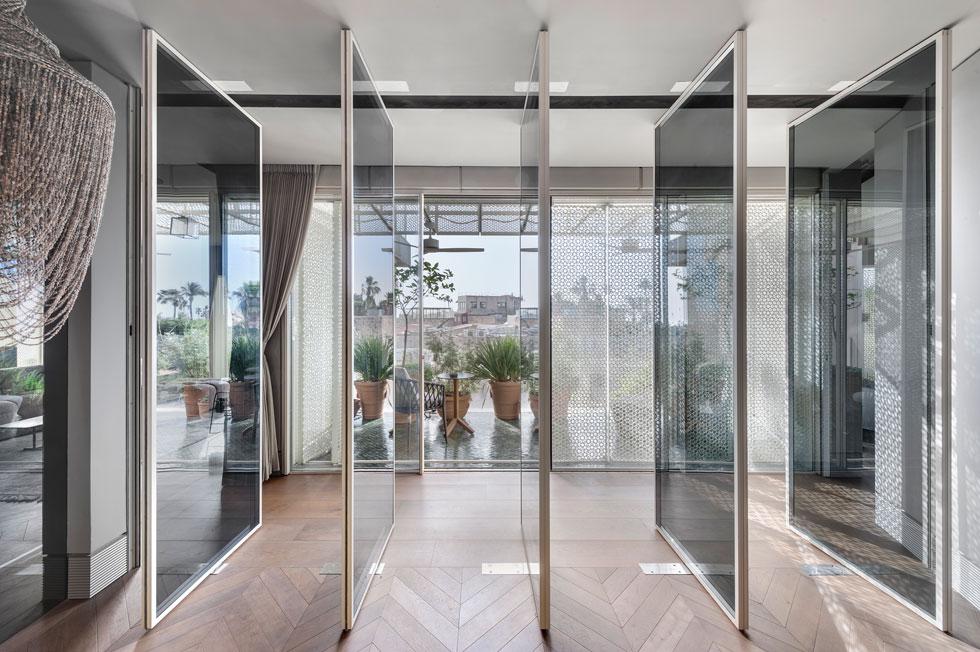 האדריכל הצליח לטשטש את חסרונותיו של המסדרון הארוך באמצעות דופן זכוכית שעיצב לחדר האורחים, ומורכבת מחמש דלתות הנעות על ציר (צילום: עודד סמדר)