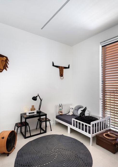 בחדר הילדים הקטן שתי מיטות עץ לבנות, שיוחלפו בקרוב במיטת קומתיים. הממ''ד יוסב לחדר ילדים נוסף (צילום: עודד סמדר)
