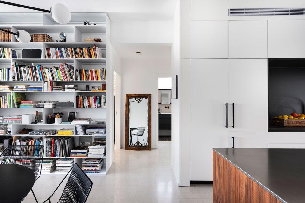 התכנון מעשי ונטול יומרות: ארונות הקיר הגדולים המשרתים את המטבח מתחלפים בסלון בספריית ברזל דקיקה ולבנה (צילום: עודד סמדר)