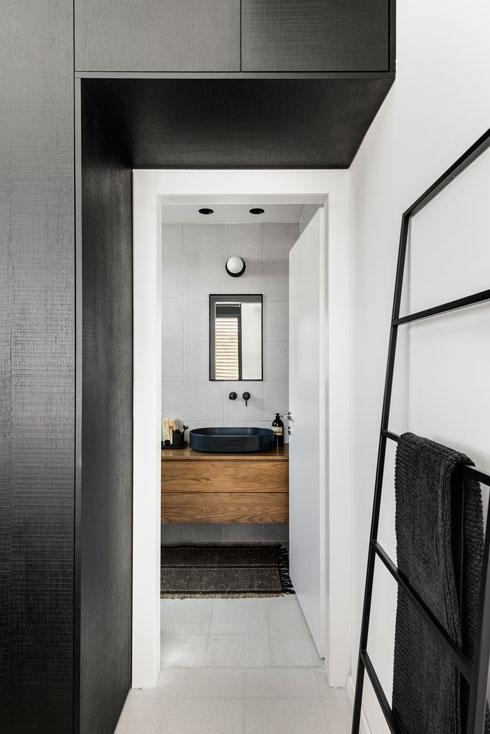 בחדר ההורים ארון קיר גבוה שמסתיר גם את מערכת המיזוג, ויוצר כניסה אינטימית יותר לחדר הרחצה הקטן (צילום: עודד סמדר)