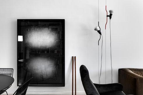 בצד אחד קיר לבן, רקע לאמנות ולפריטים נבחרים, כמו מנורת parentesi הקלאסית, שעיצבו אקילה קסטיליוני ופיו מנצו ב-1971 (צילום: עודד סמדר)