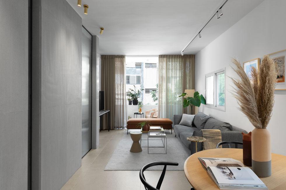 הסלון תופס את עיקר השטח כאן, ופונה אל הקיר הפיסולי של חדר הרחצה (צילום: גדעון לוין)