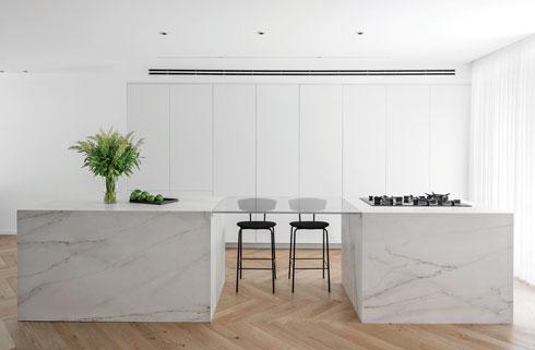 מטבח פתוח עם שני איים שמחוברים על ידי חיפוי זכוכית, המשמש גם כשולחן ישיבה גבוה  (צילום: שי אפשטיין)