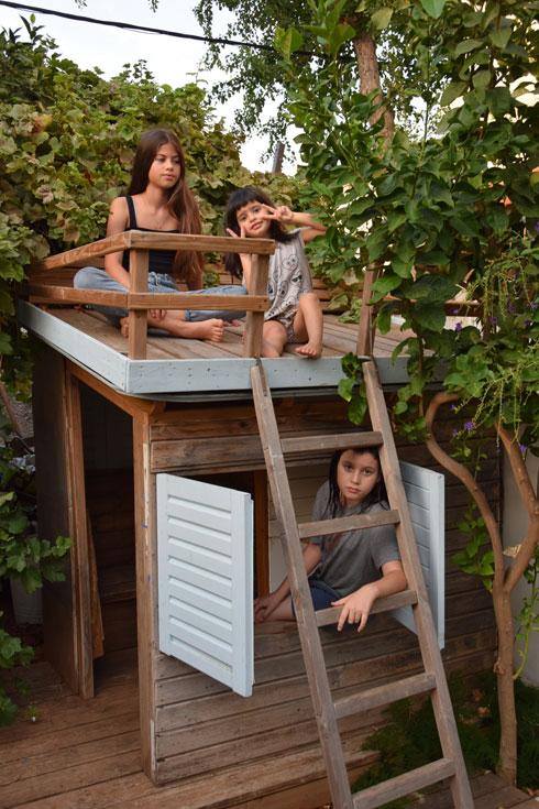 בת, אורי ואנה על גג בית המשחק שאביהם בנה בחצר. בהמשך הכתבה תוכלו לראותו מבפנים (צילום: מאיה שרון)