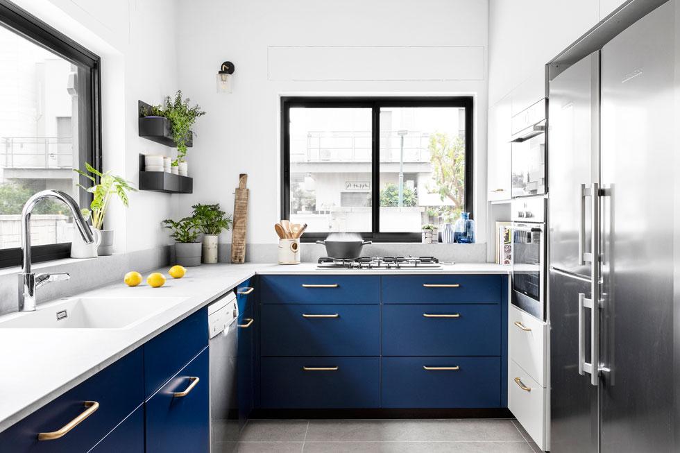 המטבח חודש והורחב. כמו בכל הבית, החלונות מוסגרו בשחור, ולדלתות הארונות נבחר צבע כחול דרמטי (צילום: איתי בנית)