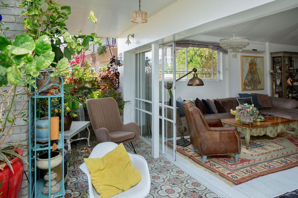 במטבח קיר מטאלי היוצר מראה עתידני ונוצץ, בניגוד מושלם למרפסת העמוסה בעציצים ירוקים (צילום: ענבל מרמרי)