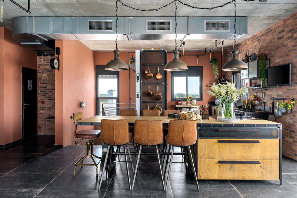 במטבח נפגש קיר שכוסה לבנים חומות בקיר שטויח בגוון חמרה חם. הארונות ושולחן האוכל הדומיננטי תוכננו בשילוב חומרים של ברזל, זכוכית משוריינת, עץ ועור. משמאל נראה גרם המדרגות היורד לקומת חדרי השינה (צילום: מאור מויאל)