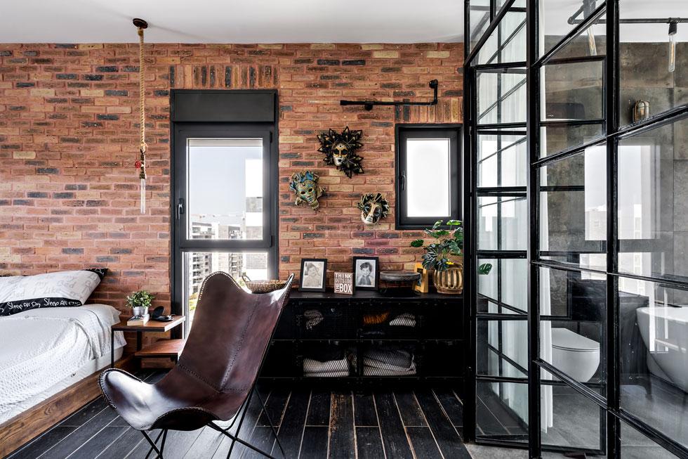 כל הרהיטים - מיטה, שידות צד ושידת מגירות - תוכננו מעץ מלא וברזל שחור. קיר ויטרינות מברזל וזכוכית מפריד בין המיטה לחדר הרחצה הצמוד (צילום: מאור מויאל)