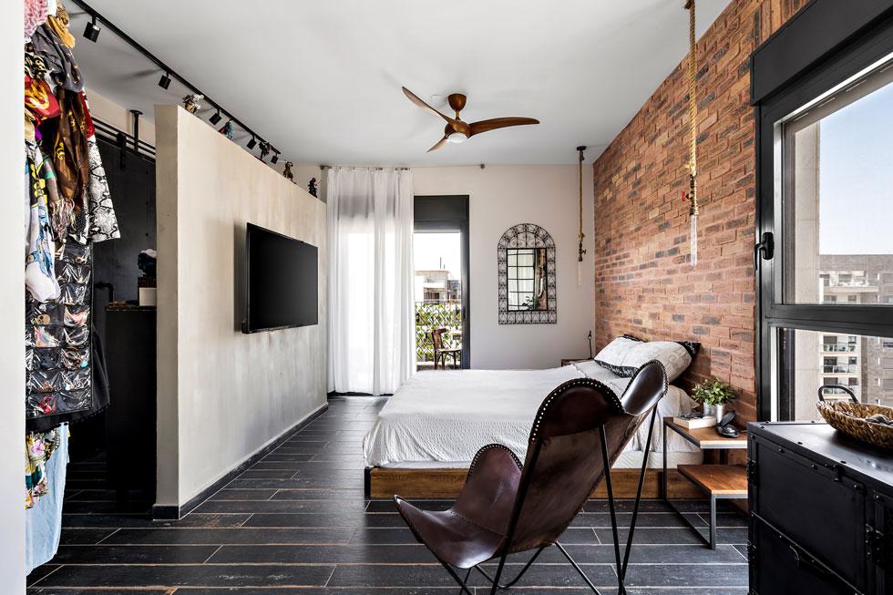 האינטנסיביות החומרית בחדר השינה היא המשך ישיר לזו שבקומת הכניסה, עם קיר לבנים בגב המיטה ורצפה דמוית פרקט מושחר (צילום: מאור מויאל)