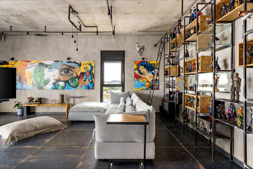 הקירות האפרפרים בסלון הם רקע לתחביב המשפחתי: קומיקס וגיבורי על. כ-3,000 בובות אספו עם השנים, וכמה מאות מהן מוצגות ברחבי הבית (צילום: מאור מויאל)