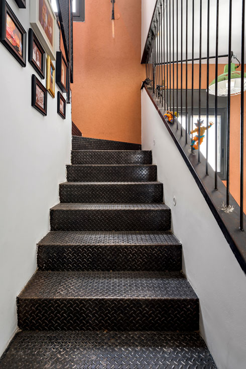 המדרגות כוסו פח מרוג שחור ולאורכן מעקות משתנים – בחלקן העליון רשת ברזל שחורה ובתחתון מוטות ברזל דקים ועגולים (צילום: מאור מויאל)