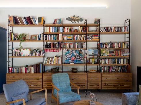 חלקה העליון של הספרייה בסלון משמש לספרים וחלקה התחתון כארונות נוספים לכלים (צילום: נגה שחם פורת)