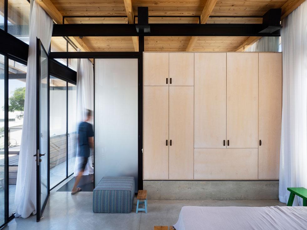 השילוב של ברזל שחור, זכוכית ועץ ליבנה בהיר נמשך גם בקומה שנוספה עבור ההורים. כאן אין קירות בכלל (צילום: נגה שחם פורת)