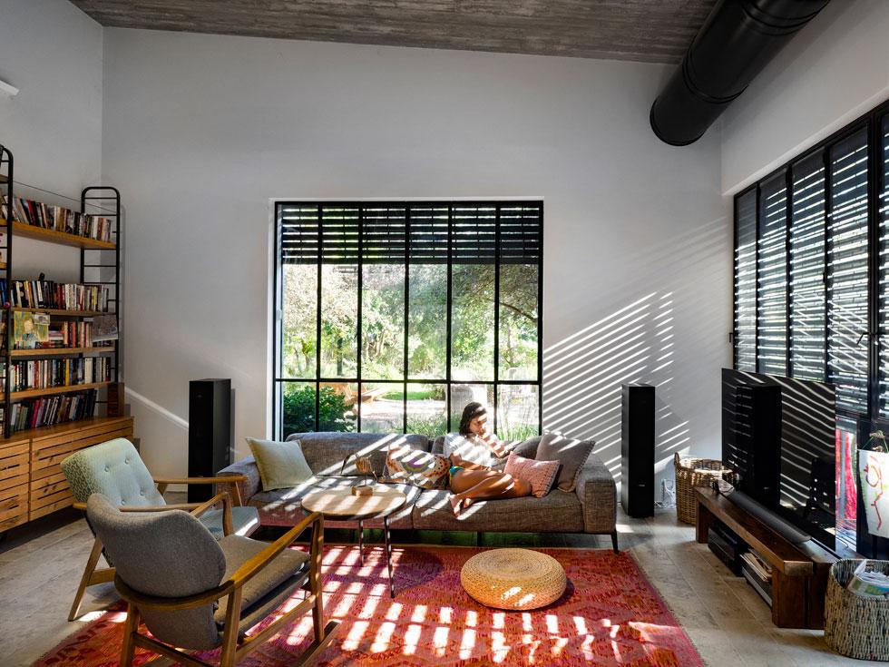 האדריכל הופקד גם על עיצוב הפנים, שכן הבית נקנה כמעטפת ריקה. בסלון ספה על רגליים דקיקות ושתי כורסאות וינטג' משופצות (צילום: נגה שחם פורת)