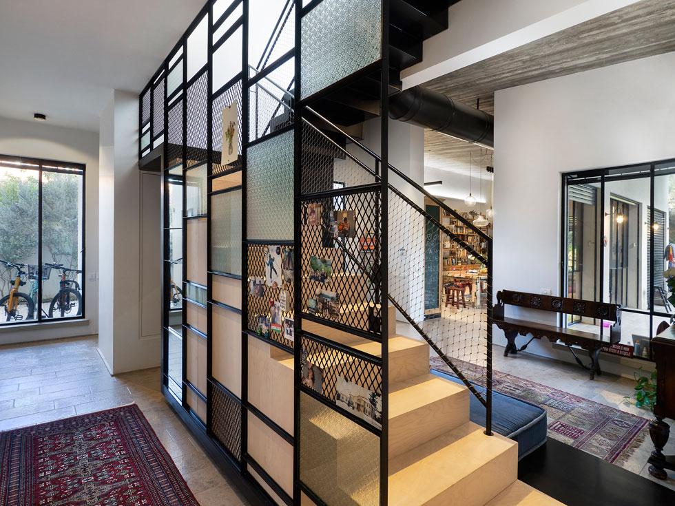 גרם המדרגות הייחודי הוא האלמנט העיצובי הבולט בבית. הוא מוקם מול הכניסה ומפריד בין החלק הציבורי לחלק הפרטי של הקומה (צילום: נגה שחם פורת)