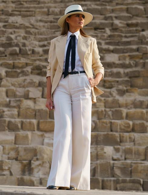 """אוקטובר 2018. את הביקור באפריקה חתמה טראמפ במראה בסגנון קולוניאליסטי שכלל מכנסיים בצבע אבן בגזרה מתרחבת, חולצה לבנה ועניבה שחורה של שאנל, ז'קט גברי מחויט בצבע בז' בעיצוב ראלף לורן ומגבעת פדורה מקש בצבע שנהב. היא נראתה מחויכת לצלמים, ובעיקר גאה במלתחה שהרכיבה בשיתוף מעצב האופנה והסטייליסט הצמוד הרווה פייר, שסיפר בראיון ל-WWD כי השניים """"בחרו לכבד את היבשת בלבוש הולם"""". טראמפ, מצדה, ביקשה מהתקשורת """"להתרכז במה שאני עושה ולא במה שאני לובשת"""" (צילום: AP)"""