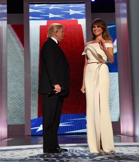 """ינואר 2017. לנשף שהתקיים בוושינגטון בערב לאחר ההשבעה בחרה טראמפ בשמלת מקסי לבנה ממשי עם כתפיים חשופות של המעצב ממוצא צרפתי הרווה פייר, כיום הסטייליסט הצמוד שלה. בראיון ל-WWD סיפר פייר כי עבד על השמלה יחד איתה: """"תהליך העבודה איתה היה מדהים. היא בעלת סגנון אישי ויודעת מה היא אוהבת. כדוגמנית לשעבר, יש לה ידע באופנה והיא מודעת לגזרות, כך שהיה לנו אוצר מילים משותף"""" (צילום: Kevin Dietsch/GettyimagesIL)"""
