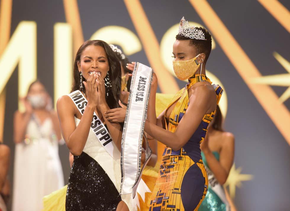 עם כתר ומסכה. מיס יוניברס זוזיביני טונזי מעניקה את הסרט לזוכה  (צילום: Benjamin Askinas/Miss Universe organization)