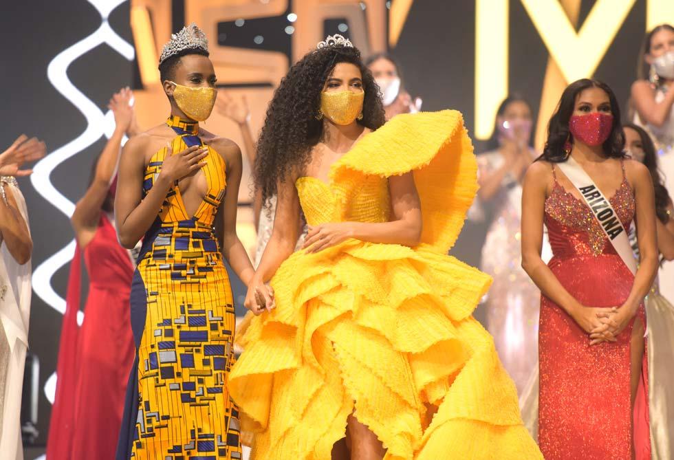 המסכות לא מסתירות את ההתרגשות. מיס USA היוצאת ומיס יוניברס מחזיקות ידיים ברגע המותח, אך שומרות על המסכות  (צילום: Benjamin Askinas/Miss Universe organization)