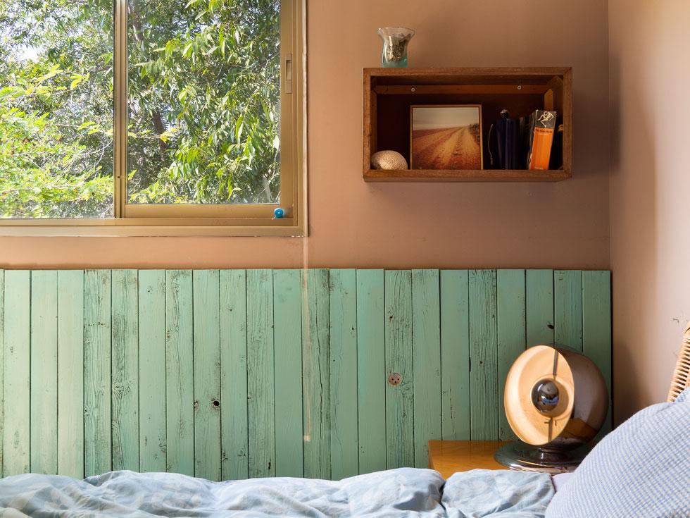 מברשת עם צבע עובדת שעות נוספות, למשל על הקרשים המשומשים שמכסים את הקיר בחדר השינה. המנורה לצד המיטה מרומא (צילום: נגה שחם פורת)