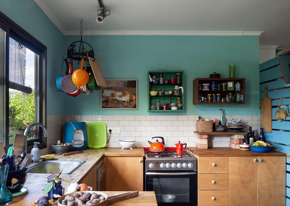 גור שיפץ את הבית עם הכניסה, לפני כעשר שנים. את המטבח תכנן והזמין מנגר, את יחידות המדפים התלויות בנה בעצמו (צילום: נגה שחם פורת)