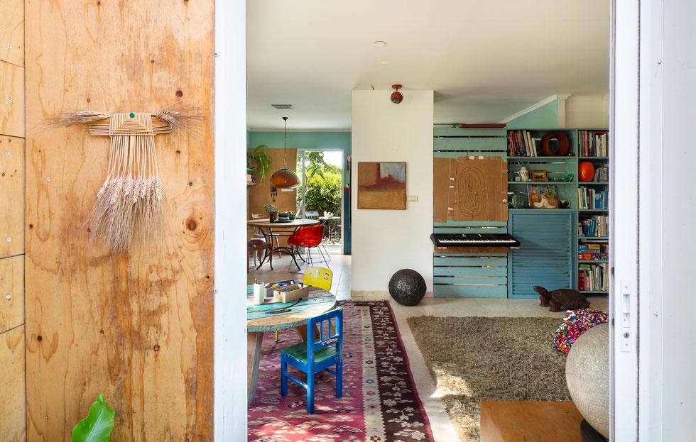 הדלת השנייה נפתחת אל סלון רך ומהוה, מלא במשחקים, ספרים ויצירה. תוספות של עץ ממוחזר, ששולבו בדרכים שונות, מחממות את האווירה (צילום: נגה שחם פורת)